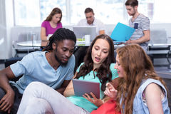 Students using digital tablet with friends in background. Smiling students using digital tablet with friends in background Royalty Free Stock Photo