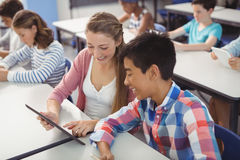 Students using digital tablet and laptop in classroom Royalty Free Stock Image