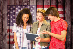 Composite image of students using digital tablet in library. Students using digital tablet in library against composite image of usa national flag Royalty Free Stock Photography