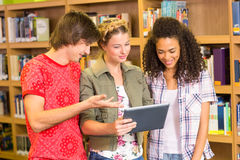 Students using digital tablet in library Stock Photography