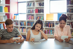 Students using digital tablet in library. At school Stock Images