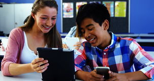 Students using digital tablet and mobile phone in classroom. At school stock video footage
