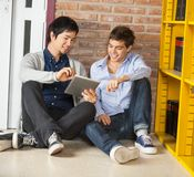 Students Using Digital Tablet While Sitting By. Happy male students using digital tablet together while sitting by bookshelf in university library Royalty Free Stock Photography