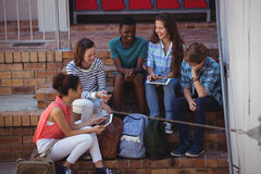 Students using digital tablet on staircase Royalty Free Stock Photo