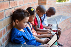 Students using dital tablet and laptop at school corridor. Students using dital tablet and laptop while sitting at school corridor Stock Photography