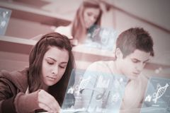 Students using futuristic hologram to learn about science from t. Ablet pc in college lecture hall Royalty Free Stock Photography