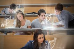 Students using futuristic interface to learn about science from. Tablet pcs in college lecture hall Royalty Free Stock Image