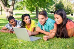 Students using laptop on campus. Group of students using laptop while lying on grass at college campus Royalty Free Stock Photos