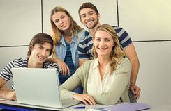 Composite image of students using laptop in classroom. Students using laptop in classroom against white tiling Stock Image