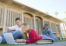 Students Using Laptop On College Campus. Happy young men and women using laptop on college campus Royalty Free Stock Photo
