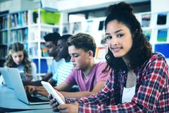 Students using laptop, digital tablet. In library Royalty Free Stock Photo
