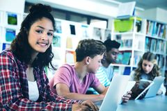 Students using laptop, digital tablet. In library Royalty Free Stock Photos
