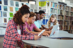 Students using laptop, digital tablet. In library Royalty Free Stock Photography