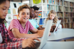 Students using laptop, digital tablet. In library Stock Images