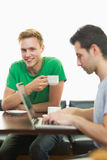 Students using laptop while having coffee at  coffee shop. Two male students using laptop while having coffee at  the coffee shop Stock Photos