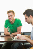 Students using laptop while having coffee at  coffee shop. Two male students using laptop while having coffee at  the coffee shop Royalty Free Stock Image