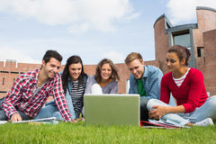 Students using laptop in lawn against college building. Group of young students using laptop in the lawn against college building Royalty Free Stock Photo
