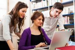 Students using a laptop in a library. Group of students using a laptop in a library Stock Photography