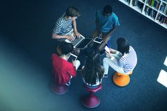 Students using laptop, mobile phone, digital tablet in library. Overhead view of students using laptop, mobile phone, digital tablet in library at school Royalty Free Stock Photos