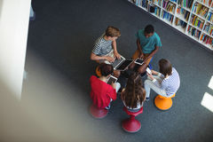 Students using laptop, mobile phone, digital tablet in library. Overhead view of students using laptop, mobile phone, digital tablet in library at school Royalty Free Stock Image