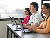 Students Using Laptops In Computer Class. Teenage boy with female classmates using laptops in computer class Stock Photo