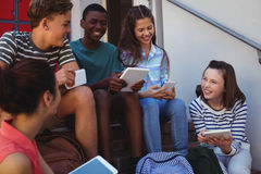 Students using mobile phone and digital tablet on staircase. At school Stock Photography