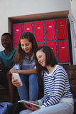 Students using mobile phone and digital tablet on staircase. At school Stock Photos