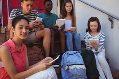 Students using mobile phone and digital tablet on staircase. At school Stock Image
