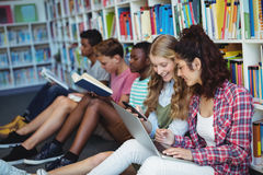 Students using mobile phone and laptop in library. At school Stock Photos
