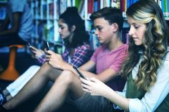Students using mobile phone in library. At school Stock Photos