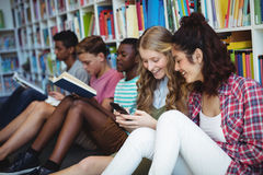 Students using mobile phone in library. At school Royalty Free Stock Photography