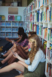 Students using mobile phone in library. At school Stock Images