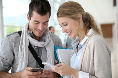 Students using smartphones in hallway Royalty Free Stock Photo