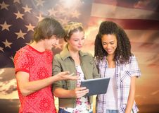 Students using tablet against american flag Royalty Free Stock Image
