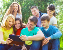 Students using tablet computer while doing homework. Young college students using tablet computer while doing homework in the park Stock Photos