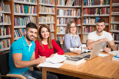 Students Using A Tablet Computer In A Library. In The Library - Handsome Group Of Students With Laptop And Books Working In A High School - University Library Royalty Free Stock Photo