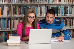 Students Using A Tablet Computer In A Library. In The Library - Handsome Two College Students With Laptop And Books Working In A High School - University Library Stock Photos