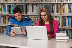 Students Using A Tablet Computer In A Library. In The Library - Handsome Two College Students With Laptop And Books Working In A High School - University Library Stock Images