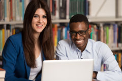 Students Using A Tablet Computer In A Library. In The Library - Handsome Two College Students With Laptop And Books Working In A High School - University Library Stock Photography