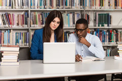 Students Using A Tablet Computer In A Library. In The Library - Handsome Two College Students With Laptop And Books Working In A High School - University Library Royalty Free Stock Photos