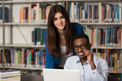 Students Using A Tablet Computer In A Library. In The Library - Handsome Two College Students With Laptop And Books Working In A High School - University Library Royalty Free Stock Photo