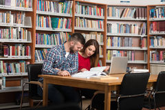 Students Using A Tablet Computer In A Library Royalty Free Stock Photography