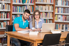 Students Using A Tablet Computer In A Library Royalty Free Stock Images