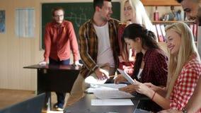 Students using tablet computer sitting desk university classroom stock video