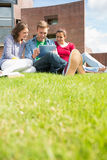 Students using tablet PC in the lawn against college building Stock Photos