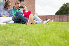 Students using tablet PC in the lawn against college building Royalty Free Stock Photos