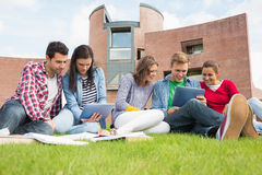 Students using tablet PCs in the lawn against college building Royalty Free Stock Photos
