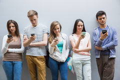 Students using their smartphones in a row Stock Photo