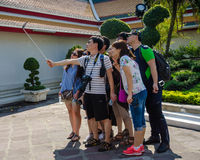 Students visiting a temple take a selfie of themselves with a cell phone. Stock Photos