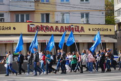 Students walk with blue flags. Stock Photos